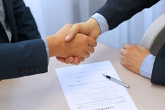 Nahaufnahme eines festen Händedrucks zwischen zwei Kollegen, nachdem ein Vertrag unterzeichnet worden ist Lizenzfreies Stockbild