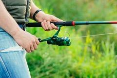 Nahaufnahme eines Fischers mit einem anziehenden Fisch der spinnenden Stange Lizenzfreie Stockfotografie