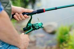 Nahaufnahme eines Fischers mit einem anziehenden Fisch der spinnenden Stange Lizenzfreies Stockfoto