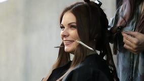 Nahaufnahme eines Frauenfriseurs, der Locken am Haar mit Brennscheren am Friseursalon macht stock footage