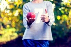 Nahaufnahme eines Frauenkörpers Frau, die Apfel hält und Daumen zeigt stockfotos