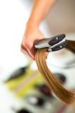Nahaufnahme eines Friseurs, der langes blondes Haar mit ha geraderichtet Stockfotografie