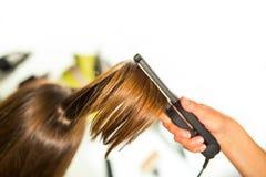 Nahaufnahme eines Friseurs, der langes blondes Haar mit ha geraderichtet Lizenzfreie Stockfotografie
