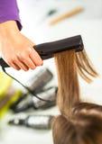 Nahaufnahme eines Friseurs, der langes blondes Haar mit ha geraderichtet Stockbilder