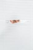 Nahaufnahme eines Geschäftsmannes, der durch Vorhänge späht Lizenzfreie Stockbilder