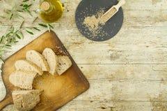 Nahaufnahme eines geschnittenen Laibs des selbst gemachten Brotes mit Samen des indischen Sesams, Ampulle des reinen Extraoliven? stockfotos