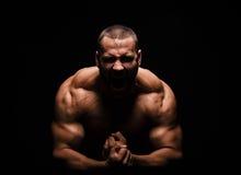 Nahaufnahme eines glücklichen Eignungsmodellmannes mit einem muskulösen Körper auf einem schwarzen Hintergrund Ein starker Mann m lizenzfreie stockfotografie