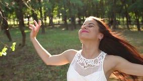 Nahaufnahme eines glücklichen Mädchens mit dem flüssigen Haar gehend in einen Sommer Park bei Sonnenuntergang stock footage