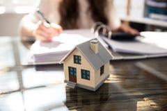 Nahaufnahme eines Haus-Modells On Glass Desk stockfotografie