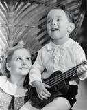 Nahaufnahme eines Jungen, der eine Gitarre mit seiner Schwester spielt (alle dargestellten Personen sind nicht längeres lebendes  Lizenzfreie Stockbilder