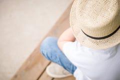 Nahaufnahme eines Jungen in einem Strohhut, der auf der Holzbank - Ansicht von der Spitze sitzt Lizenzfreie Stockfotografie