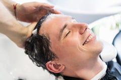 Nahaufnahme eines jungen kaukasischen Mannes, der sein Haar sich waschen lässt in einem Frisörsalon lizenzfreie stockfotos