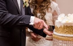Nahaufnahme eines Jungvermähltenpaare ` s übergibt den Schnitt ihrer Hochzeitstorte stockfotografie