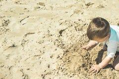 Nahaufnahme eines Kindes, das im Sand auf dem Strand spielt Lizenzfreies Stockfoto