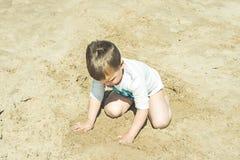 Nahaufnahme eines Kindes, das im Sand auf dem Strand spielt Lizenzfreie Stockbilder