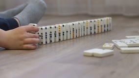 Nahaufnahme eines kleinen Jungen, der einen weiten Weg von Dominos mit mehrfarbigen Punkten errichtet stock video footage