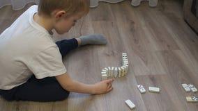 Nahaufnahme eines kleinen Jungen, der einen weiten Weg von Dominos mit mehrfarbigen Punkten errichtet stock video