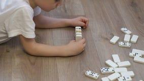 Nahaufnahme eines kleinen Jungen, der mit Dominos auf dem Boden des Hauses spielt stock footage