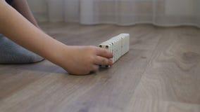 Nahaufnahme eines kleinen Jungen, der mit Dominos auf dem Boden des Hauses spielt stock video