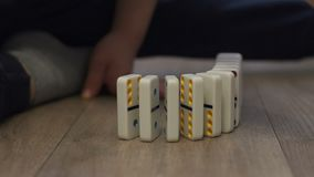 Nahaufnahme eines kleinen Jungen, der mit Dominos auf dem Boden des Hauses spielt stock video footage