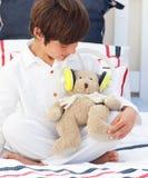 Nahaufnahme eines kleinen Jungen, der mit einem Teddybären spielt Lizenzfreie Stockfotos