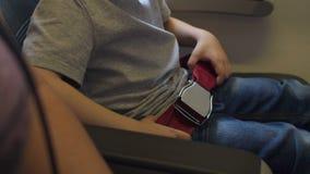 Nahaufnahme eines kleinen Kindes befestigt Sicherheitsgurte in einem Flugzeug stock video footage