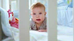Nahaufnahme eines kleinen Kleinkindes in einer Krippe Seitenansicht durch das Gitter einer Krippe lachend Glückliche Kindheit, ki stock video