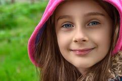 Nahaufnahme eines kleines Mädchen ` s Gesichtes mit der Haube, die Kamera betrachtet und stockfoto