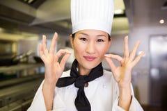 Nahaufnahme eines lächelnden weiblichen Kochs, der okayzeichen gestikuliert Stockbilder