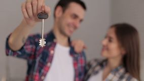 Nahaufnahme eines liebevollen Paares, das den Schlüssel zu ihrer neuen Wohnung, Fokus auf Schlüssel hält stock video