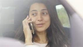 Nahaufnahme eines Mädchens, das am Telefon im Auto spricht Langsame Bewegung stock video