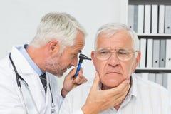 Nahaufnahme eines männlichen Doktors, der das Ohr des älteren Patienten überprüft stockbild