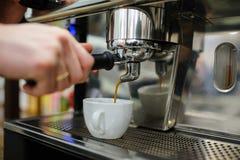 Nahaufnahme eines Mann barista, das einen Espresso unter Verwendung eines Kaffeemachs braut lizenzfreie stockbilder