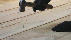 Nahaufnahme eines Mannes, der einen benutzten Nagel in Bretter hämmert Sonderkommando der Arbeitskraft mit einem Nagel und einem  stock video