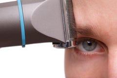 Nahaufnahme eines Mannes mit einem Trimmer an seiner Augenbraue, lokalisiert auf einem weißen Hintergrund Lizenzfreie Stockbilder