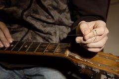 Nahaufnahme eines Mannes mit einer Gitarrenschnur wird zerrissen Stockfotos