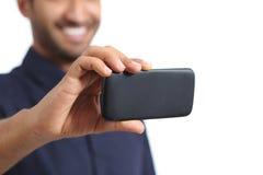 Nahaufnahme eines Mannhandaufpassenden Videos in einem intelligenten Telefon Lizenzfreie Stockfotos