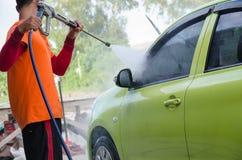 Nahaufnahme eines Mechanikers Washing ein Auto durch Druckwasser an der Garage stockfotografie