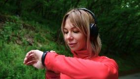 Nahaufnahme eines recht blonden Mädchens in den laufenden Kopfhörern, die im Wald stehen, bevor ihre Eignung gerüttelt wird und b stock footage