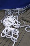 Nahaufnahme eines Schiffstaus mit einem geknoteten Ende gebunden um einen Bügelen auf einem Seeschiffstau des hölzernen Piers Lizenzfreie Stockfotos