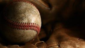 Nahaufnahme eines schmutzigen, alten Baseballs mit Rotnähten auf einem braunen Lederhandschuh lizenzfreie stockfotografie