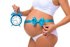 Nahaufnahme eines schwangeren Bauches mit einem blauen Band und einem Wecker Konzept der Schwangerschaft Lizenzfreie Stockbilder