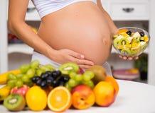 Nahaufnahme eines schwangeren Bauches mit frischer Frucht und Platte des Salats Lizenzfreies Stockbild