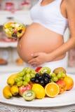 Nahaufnahme eines schwangeren Bauches mit frischer Frucht und Platte des Salats Gesunde Schwangerschaft, Diät und Vitamine Stockfotos
