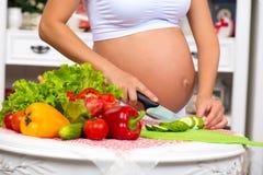 Nahaufnahme eines schwangeren Bauches Schwangere Frau in der Küche, die einen Gemüsesalat zubereitet Lizenzfreies Stockbild