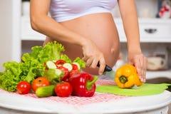 Nahaufnahme eines schwangeren Bauches Schwangere Frau in der Küche, die einen Gemüsesalat zubereitet Lizenzfreie Stockfotografie