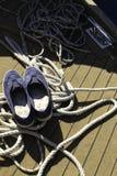 Nahaufnahme eines Seils mit einem geknoteten Ende gebunden um einen Bügelen auf einem hölzernen Pier und Schuhen mit Ankern Lizenzfreie Stockbilder