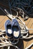 Nahaufnahme eines Seils mit einem geknoteten Ende gebunden um einen Bügelen auf einem hölzernen Pier und Schuhen mit Ankern Stockbilder