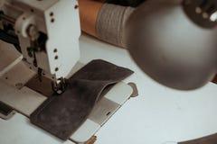Nahaufnahme eines Stückes Leders auf dem Tisch liegend auf einer Nähmaschine in der Werkstatt Handgemachter Meister bei der Arbei stockbilder