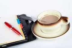 Nahaufnahme eines Tasse Kaffees mit dem Löffel inner und Notizbuch mit Ballpoint stockfoto